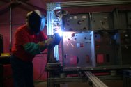 Worker Welds Metal Cabinet